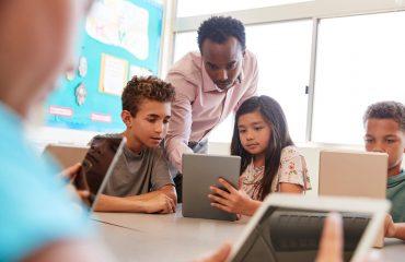 crianças fazendo dinâmica de grupo para alunos junto do professor utilizando um tipo de mídia diferente do tradicional